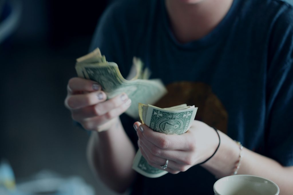 close up of hands and dollar bills